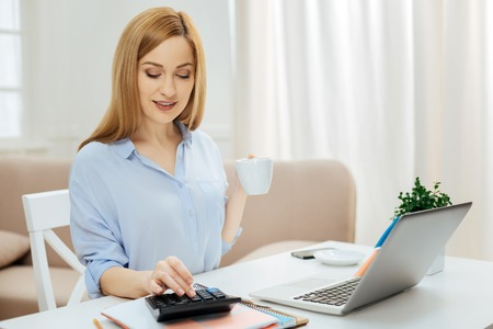 Coffee time. Beautiful self-assured successful young blond woman smiling and wearing a blue shirt while working on her laptop and using calculator and holding a cup of coffee