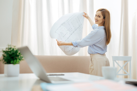 Satisfied. Happy smiling blond young businesswoman standing at the window and holding a big drawing and looking back at her working table