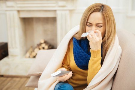 Sneezing. Sick unhappy young dark-eyed woman having runny nose and sneezing and sitting on the couch and holding remote control and a fireplace in the background Stock Photo