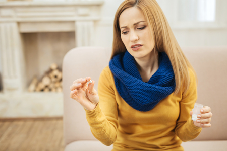 Oh no. Ill young blond long-haired woman wearing a scarf jeans and sweater and sitting on the couch while holding a pill and looking at it with disgust and a fireplace in the background