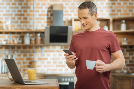 Waiting for you. Attractive male person keeping smile on his face and looking at telephone while standing in the kitchen Reklamní fotografie