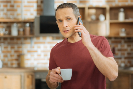 I am in all ears. Confident man being very attentive while talking per telephone and holding cup in right hand
