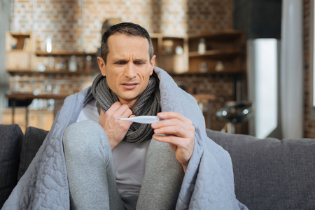 It is a problem. Serious ill man wrinkling forehead while touching scarf and checking his temperature