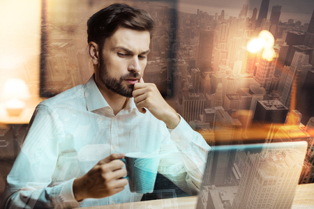 Careful planning. Handsome young man in a white shirt sitting at the table in front of a laptop, drinking coffee and thinking about his work agenda