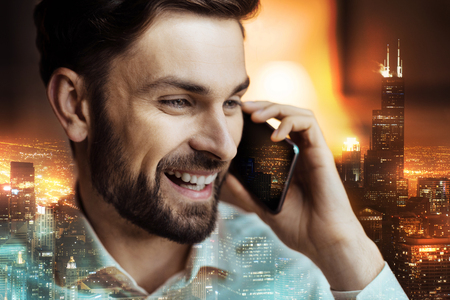 Good news. The close up of a handsome dark-haired young man talking on the phone and smiling broadly, listening to great news, while being against an night urban background