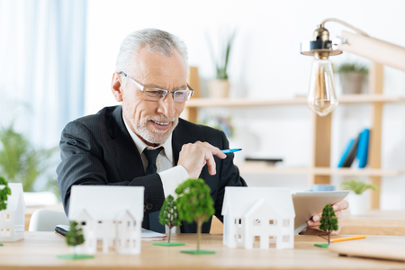Cheerful excited professional real estate agent feeling satisfied with the results of his work and smiling while looking at the wonderful miniatures of beautiful houses