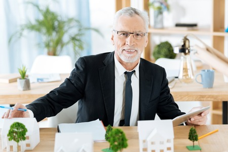 Cheerful realtor. Positive enthusiastic smart realtor looking glad while being in his beautiful comfortable office and sitting at the table with a modern tablet in his hand