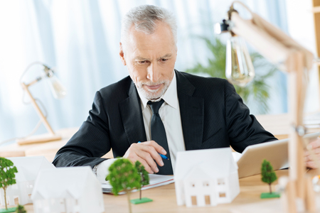 Concentration. Responsible calm qualified real estate agent looking attentively at the lovely miniature of a pretty white house and thinking about its quality