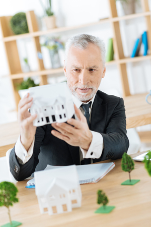 Nice work. Clever experienced worker of a real estate agency sitting in his office with a wonderful miniature of a house in his hands and looking attentive while thinking about it Foto de archivo