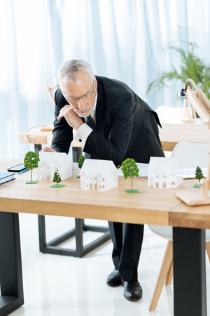 Serious. Smart experienced serious real estate agent looking at the tiny miniature houses on his table and looking concentrated while thinking about their selling Stock Photo