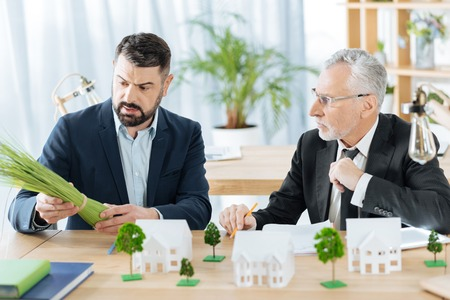Strange plants. Surprised aged realtor looking at his calm colleague sitting by his side and holding a bunch of herbs in his hands Stock Photo