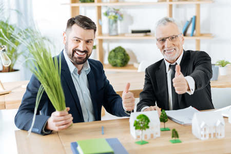 Happy colleagues. Emotional successful real estate agents feeling glad while sitting at the table in their comfortable office with their thumbs up and celebrating their productive day Stock Photo