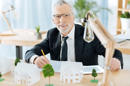 Confident worker. Clever attentive responsible worker of a real estate agency sitting at the table with lovely miniature houses and trees by his side and making important notes