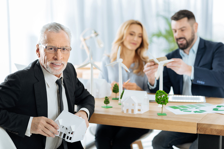 Successful project. Pleasant cheerful aged man sitting at the table with a lovely little house in his hands while his friendly colleagues sitting not far from him