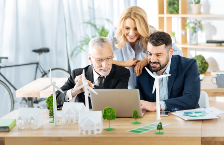 Feeling happy. Clever positive team of engineers feeling glad while being in their beautiful office and looking attentively at the screen of a modern laptop Stock Photo
