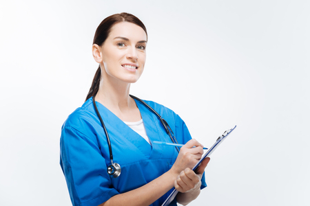 Describe your pain. Appealing glad female doctor  posing on the isolated  background  while writing  information and holding blue folder