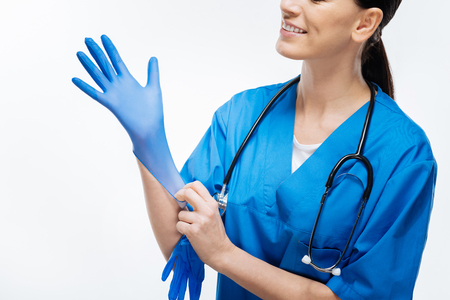 First gloves. Close up of tender female doctor hands when she wearing gloves while posing and has stethoscope Stock Photo