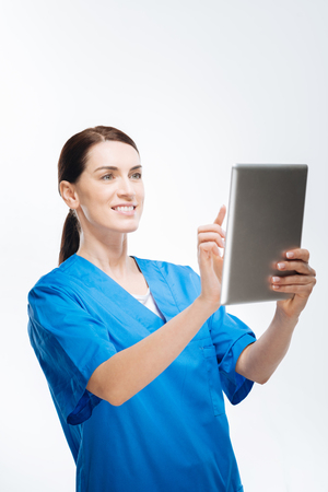 Future of medicine. Ambitious cute female doctor pointing at tablet while smiling on isolated background and looking at screen