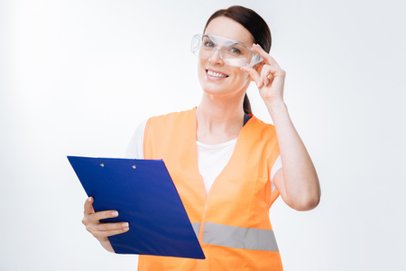 Plan execution. Pleasant good looking female engineer has folder while laughing and touching safety glasses