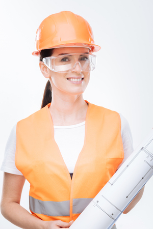 Complete work. Charming happy female architect smiling and holding blueprint while posing on the isolated background