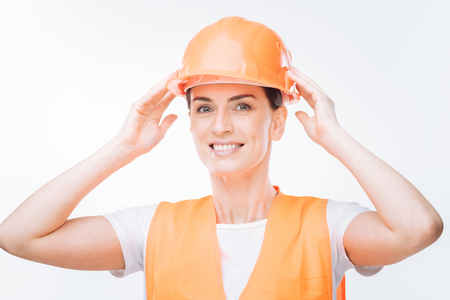 Construction site. Optimistic cheerful female worker  dressing in safety vest while smiling on the isolated background and holding hard hat above the head Stock Photo