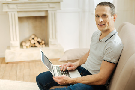 Feeling good. Young smart handsome man looking positive while sitting on a soft sofa with a modern convenient laptop on his knees and smiling