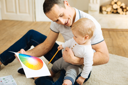 Little helper. Cute pretty little child sitting with a kind loving cheerful father and holding a pencil while helping him to work with color palettes Stock Photo