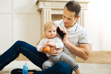 Hello darling. Kind attentive loving father sitting on the floor in a beautiful room with a smartphone in his hand and organizing a phone talk for his little pretty child Stock Photo