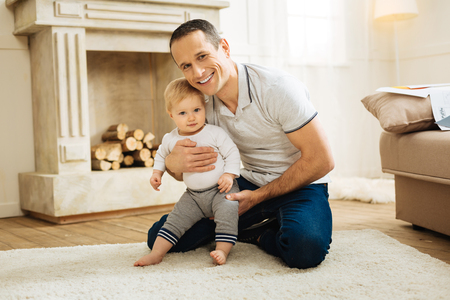 Lovely atmosphere. Pleasant kind attentive father feeling happy while being at home and hugging his adorable cute little child