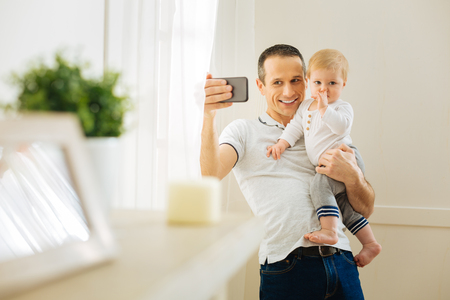 Delighted father. Cheerful emotional young man standing near the big window and smiling while holding a baby and taking photos with him Stock Photo