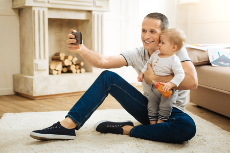 Cute photo. Emotional cheerful young father sitting on the floor and taking photos with his cute surprised baby while spending a good time together