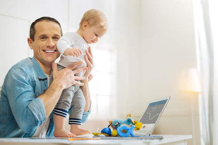 Stand still. Attentive responsible enthusiastic father looking happy while helping his cute lovely baby to stand on the table in front of a modern laptop