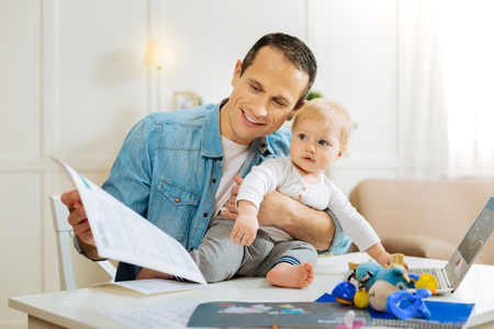 New activity. Adorable little calm child feeling glad while sitting on the table next to the modern laptop and smiling while a loving kind smart father sitting near and working