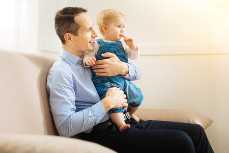 Watching film. Cheerful calm relaxed father sitting on the sofa and holding a little child while watching an interesting film together
