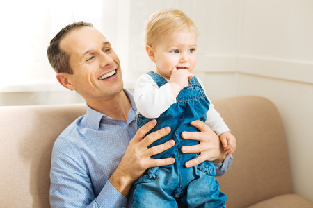 Adorably serious. Pleasant attentive father smiling while seeing his adorable little child putting his finger into his mouth while being concentrated during watching a nice cartoon