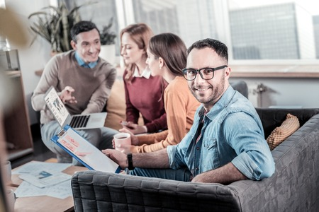 My team. Bespectacled handsome smiling man sitting on the sofa near his colleagues holding the tablet and looking straight. Stock Photo