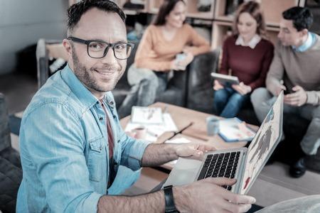 My laptop. Handsome unshaken joyful man holding the laptop looking straight and smiling.
