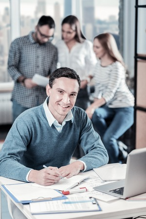 Work continuation. Smiling confident occupied man sitting by the table holding a pan and writing. Stock Photo