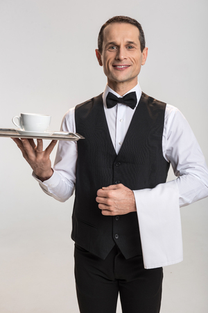 Your tea. Attractive  vigorous male waiter  standing on the grey background and looking at the camera  while bringing  salver