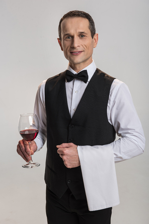 Excellent catering. Professional jolly male waiter standing on the grey background and  staring at the camera while serving wine Foto de archivo
