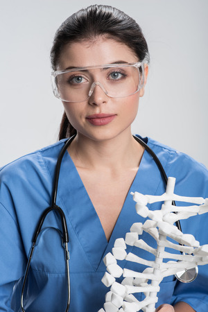 Biological enigma.  Serious beautiful female doctor has stethoscope while wearing safety glasses and looking straight Stock Photo