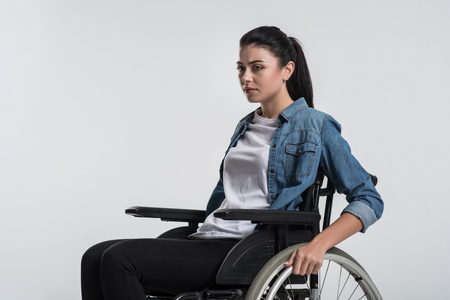 Serious problem. Beautiful nice crippled woman posing on the isolated background while sitting in the wheelchair and thinking Stock Photo