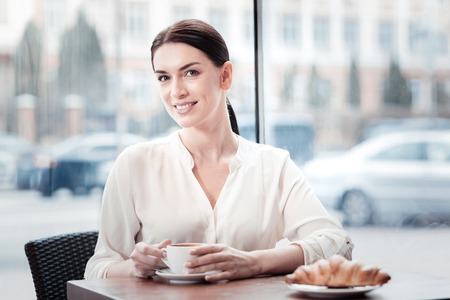 Delighted young woman keeping smile on her face while looking forward and holding cup in both hands