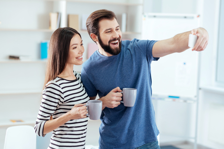 Selfie for lovers. Appealing positive successful couple taking selfie while smiling  and have lunch