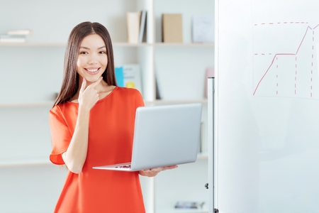Tricky problem. Elegant young joyful woman  smiling near white board while touching her chin  and carrying laptop