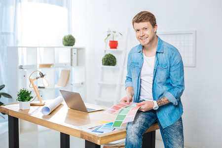 Color palettes. Cheerful handsome positive designer sitting on the table and smiling while holding bright color palettes