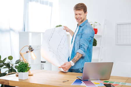 Confident skilled experienced engineer standing near the table with a big drawing in his hands and smiling while looking at the screen of his modern laptop