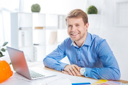 Happy employee. Cheerful smart enthusiastic engineer sitting in front of a modern laptop in his light comfortable office and smiling while feeling happy