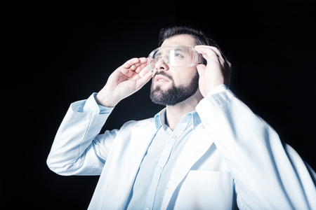 Lab worker. Smart nice bearded man standing against black background and looking up while fixing his safety glasses Stock Photo