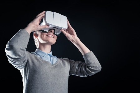 Portable device. Positive nice young woman holding virtual reality glasses and looking into them while standing against black background Stock Photo